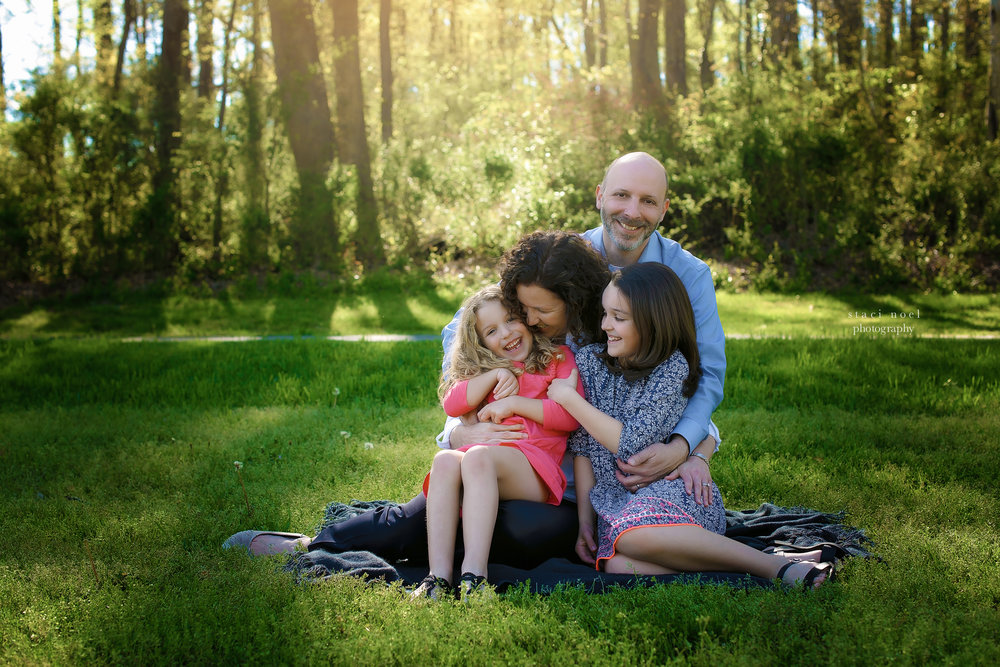 charlotte's best family photographer staci noel photographer captures family images mother, father and daughters in park setting outdoors in natural light