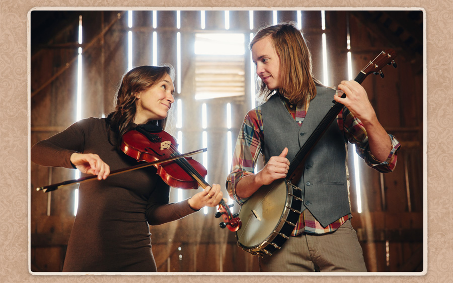 Eric and Ellie in a hayloft jamming out on banjo and fiddle for their engagement session with McClanahan Studio on the family farm. Sunlight streaming through barnboard look epic.