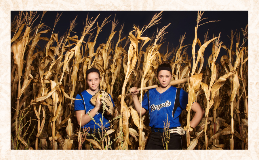 Twins Madison and McKenna Farren pose for a softball senior portrait in a Colo, IA, corn field