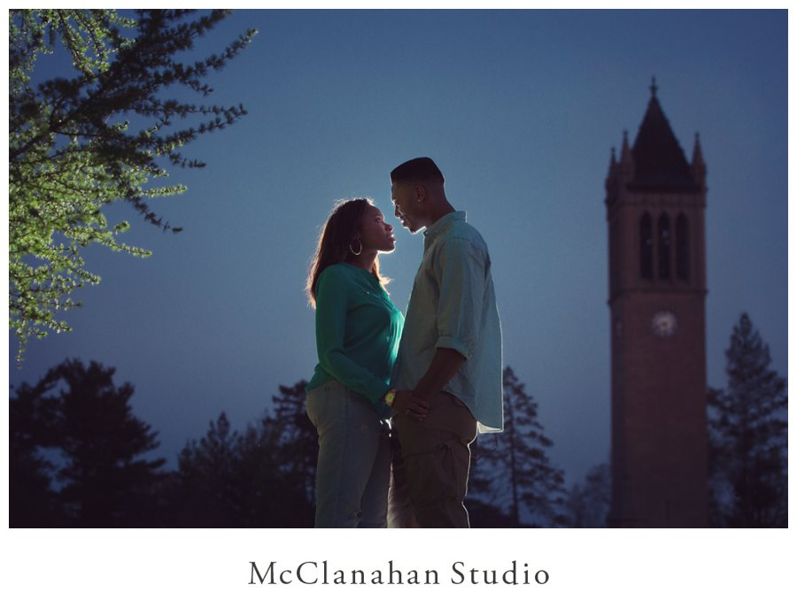 Backlit portrait of Iowa State University grads Melvin Ejim and Samantha Melvin on campus at dusk with the Campanile.
