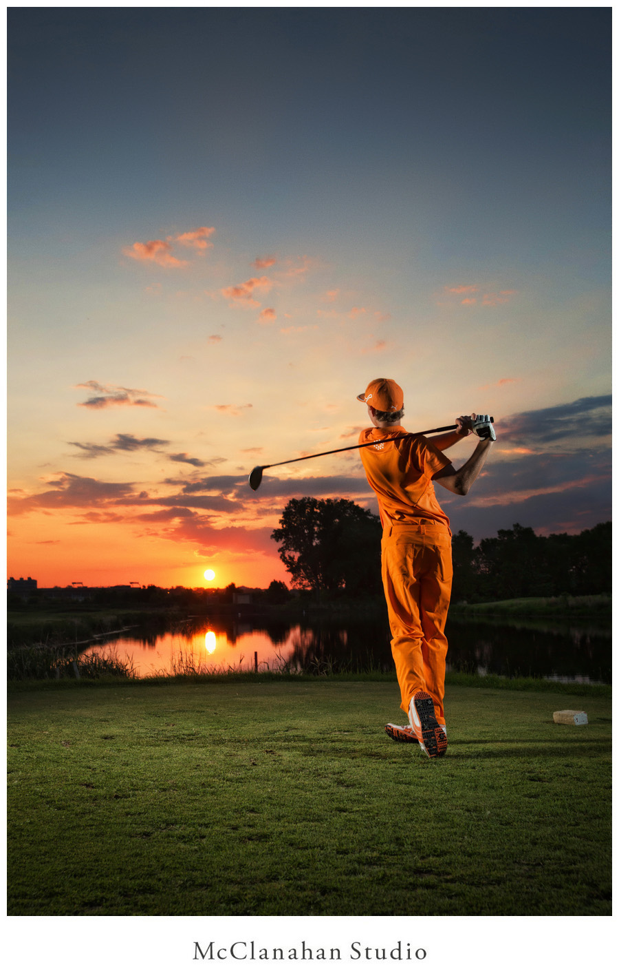 Epic senior photograph of Lyle Kuhlmann driving the first hole at Coldwater Golf Links in Ames, IA. Beautiful sunset reflecting on the water to match Lyle's rad orange golf outfit. Portrait created by internationally renowned Ames portrait photographer McClanahan Studio.