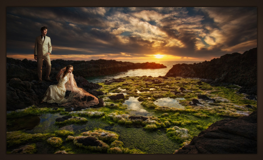 Bride and groom portrait lounged on the rocky Oregon coast with an epic sunset behind. Des Moines Photographer McClanahan Studio photographed this image. Destination wedding. Photo was selected for the 2014 PPA Loan Collection.