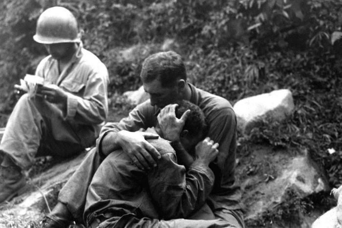 A grief stricken American infantryman whose buddy has been killed in action is comforted by another soldier. In the background a corpsman methodically fills out casualty tags, Haktong-ni area, Korea. August 28, 1950. Sfc. Al Chang. (Army)  (  U.S. Army Korea Historical Image Archive/ Flickr )