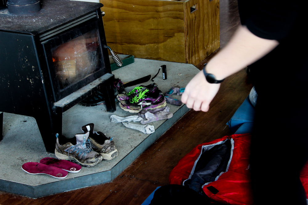Hikers use the heat from the wood burning stove to dry their shoes, socks and clothing after a rainy day of hiking.