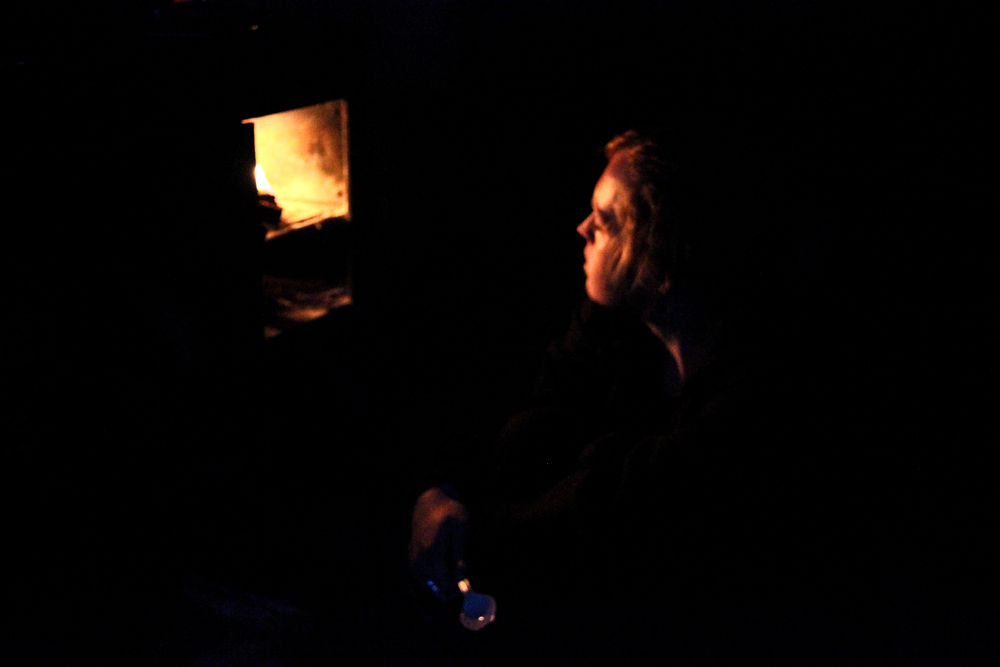 Jamie stokes the fire in Castle Rocks Hut's wood burning stove on our second night. The stove is the hut's only source of heat, and drinking water had to be boiled or treated.