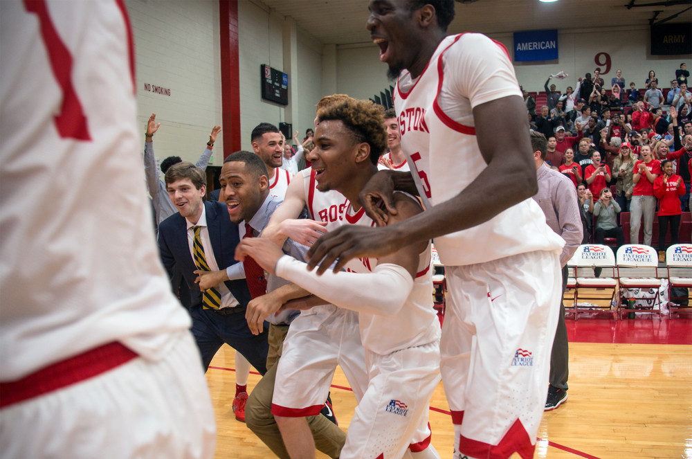 Cheddi Mosely (center), Blaise Mbargorba (right), and the rest of the men's basketball team react as guard John Papale breaks a tie in the final moments to defeat Lehigh University 75-73 in Boston University's Case Gym in Boston, Mass., on Jan.31, 2016.