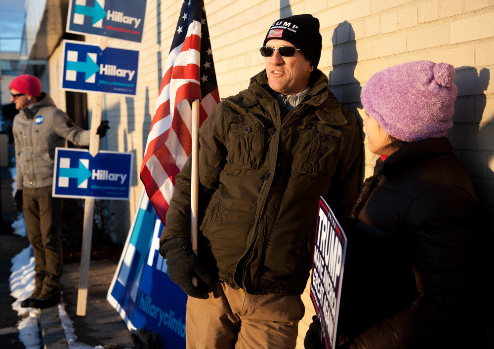 Manchester, NH, Feb. 9, 2016 - Greg Salts (center) and his daughter Hannah Salts, both of Manchester, campaign in support of Donald Trump by the entrance of a polling station at the Manchester Health Department. Salts said he has been voting in the same precinct for over 20 years. Photo by Alexandra Wimley