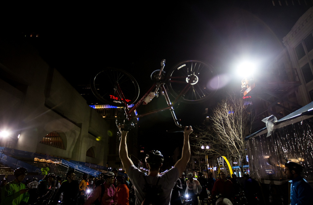 Dan Wiese lifts his bike for a photo at the Boston Marathon finish line after completing the Midnight Marathon Bike Ride, which begins at midnight on April 18 in Hopkington, Mass., and traverses the route of the Boston Marathon.