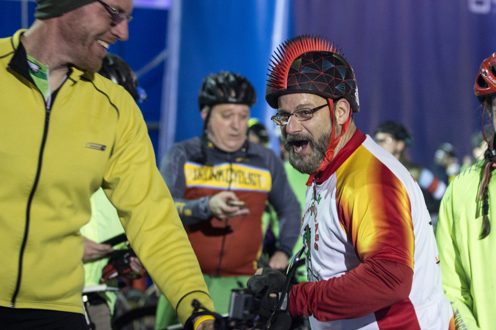 Dan Brossi (right) talks with fellow participants after completing the Midnight Marathon Bike Ride, which begins at midnight on April 18 in Hopkington, Mass., and traverses the route of the Boston Marathon.