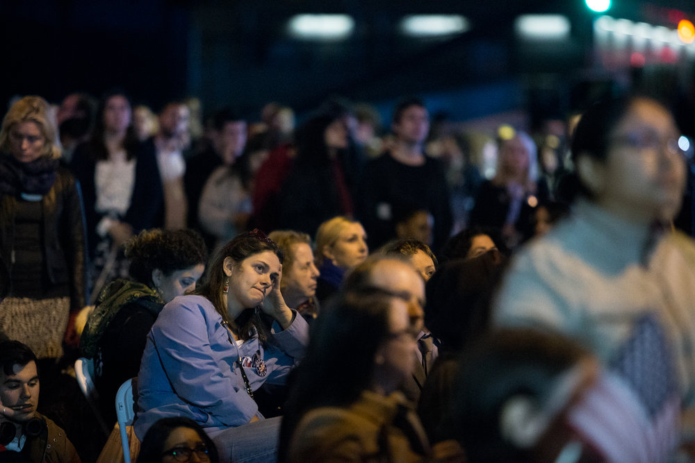 "Attendees watch commentary and results on the big screen television outside the Jacob K. Javits Convention Center, in the early hours of Nov. 9, 2016. After it became clear that Clinton would lose, attendees waited to find out if she would make a concession speech that night. Soon after, Clinton's campaign manager John Podesta announced that Clinton will not be speaking until the next day and urged supporters to go home and ""get some sleep"". ""They're still counting votes and every vote should count,"" Podesta said. ""Several states are too close to call, so we're not going to have anything more to say tonight."""