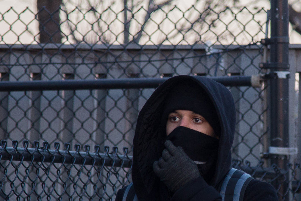 A man shields his face against the cold while walking down Commonwealth Ave in Boston as windchill temperatures reached as low as minus-24 in some areas of New England on Dec. 16, 2016.