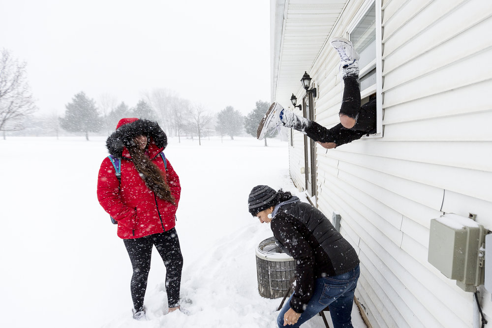 Alysia Powless, from left, and Tina Christjohn, Joey Powless's girlfriend, laugh as Jojo Powless climbs through a window of his house after being locked out in Oneida, Wis., Wednesday, December 13, 2017. Jojo Powless lit the fire initially, which his father Joey Powless said was symbolic of the innocence of young people and the power they have to positively influence the community.