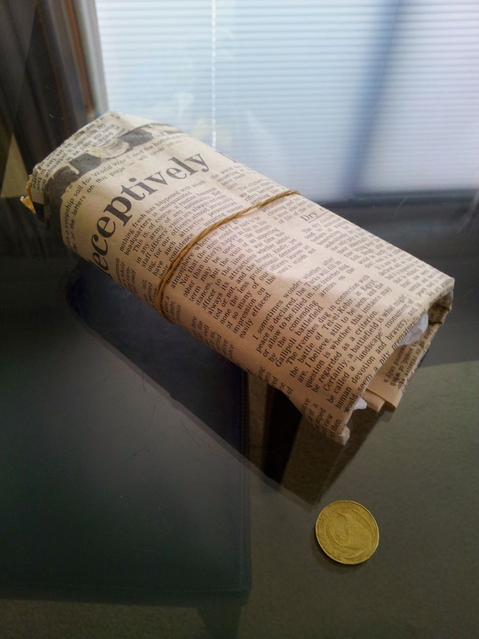 The camera wrapped in a newspaper talking about ...?. (looks like about cameras... can we get a scan of the newspaper?)