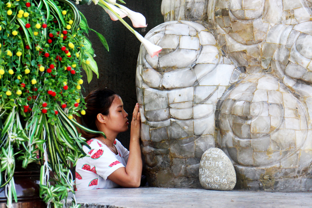 Woman praying underneath the statue of Our Lady of La Vang