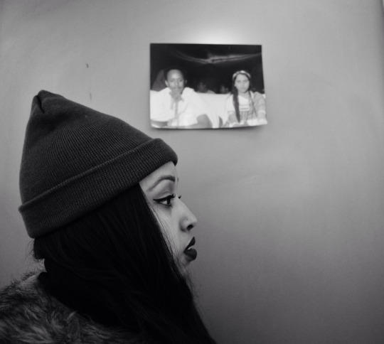 Warsan standing with a picture of her parents.