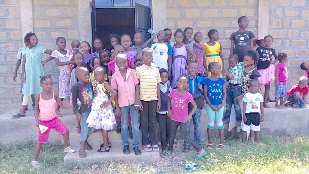 "These kids.     Posing outside the Resource Center.     Safe.     Learning about Jesus.     Having fun.  You helped make this happen. Providing a quality Christian place for vulnerable kids to gather and know they are loved.  Inside that door are games, art supplies, books, toys and teachers who care that these little ones are not left to neglect and abuse.  ""Asante sana Everybody!"""