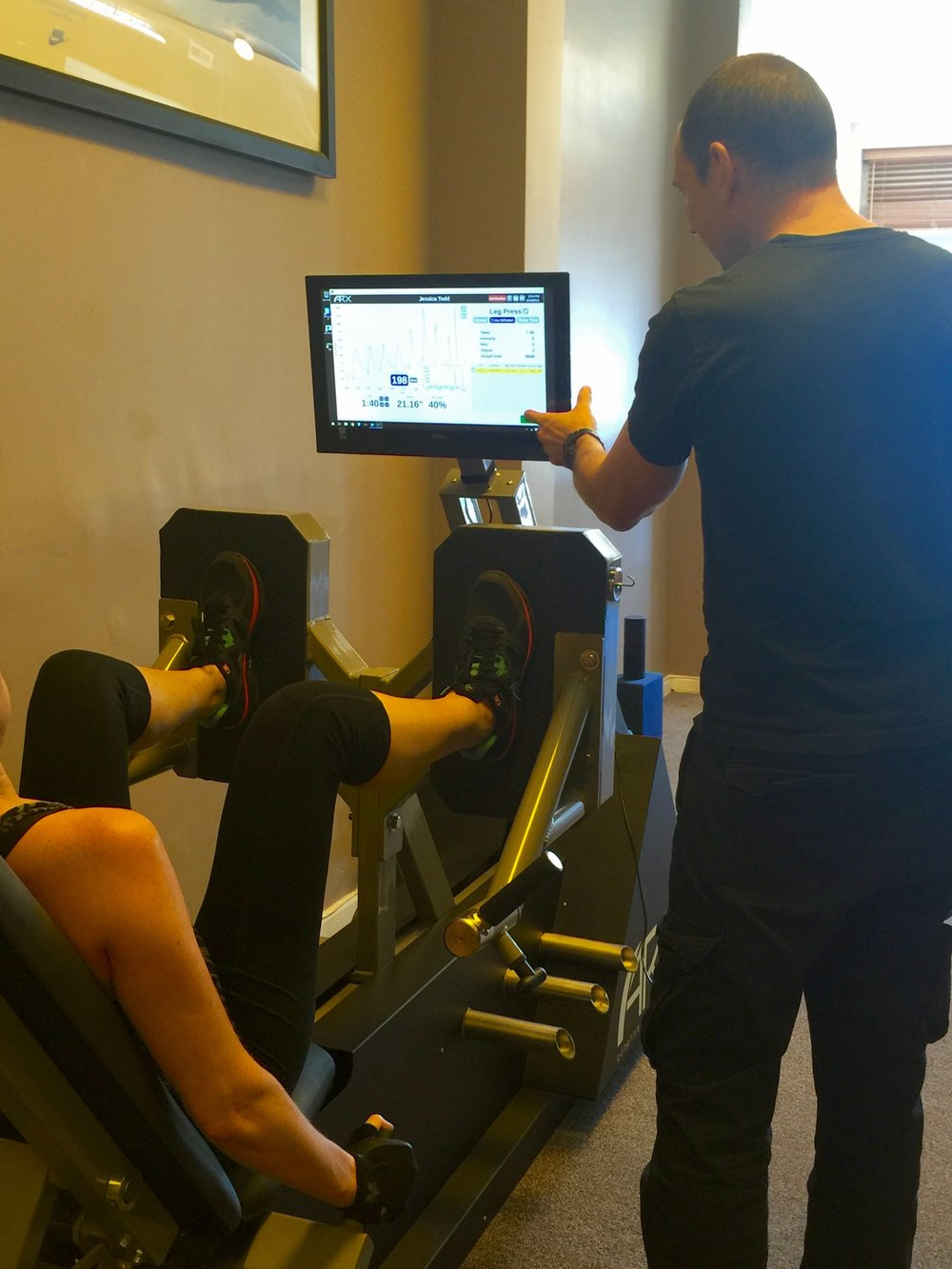 Client performing leg press on ARX Alpha Strength Training Unit