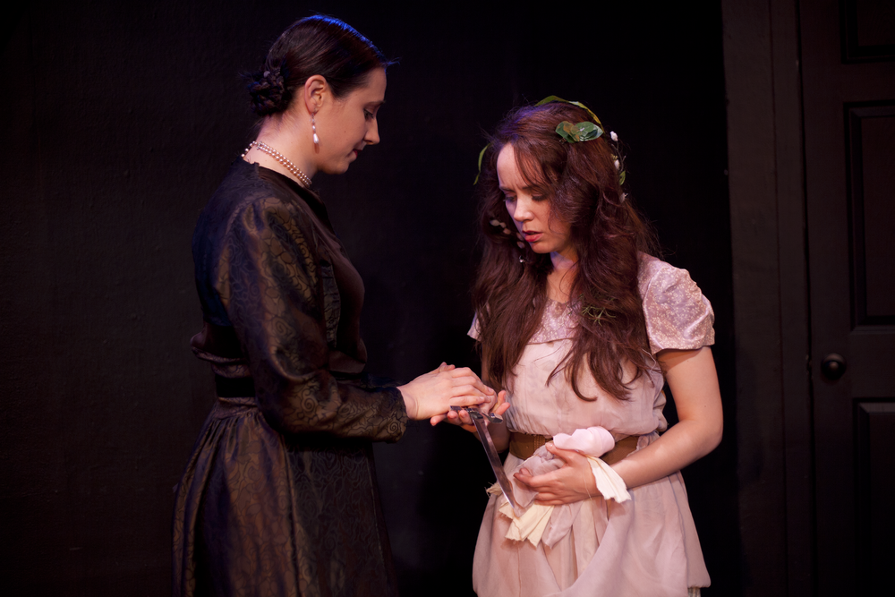 Production image of Gertrude (Sarah Eismann) and Ophelia (Gwenevere Sisco) in  May Violets Spring  when produced with  Dare Lab  at The Bridge Theatre in Spring 2014.  Photographs by  Trish Phelps .