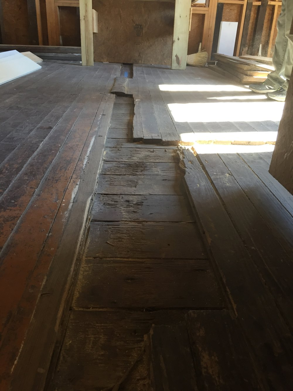 Ghost marks left in the wood floor by a wall and doorway that used to divide the room.