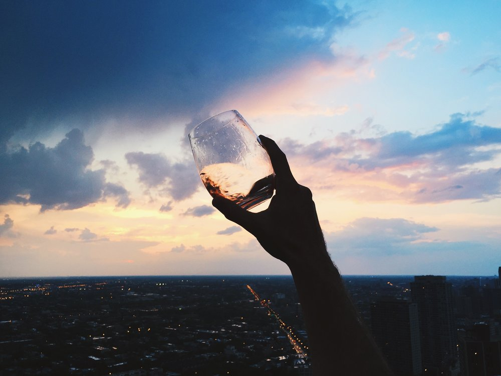 """John holding up his glass of rosé against the sky. This was an evening that it was storming like crazy in Chicago and then there was a brief hour where the sky was a watercolor painting and we were relaxing with a bottle of rosé. """