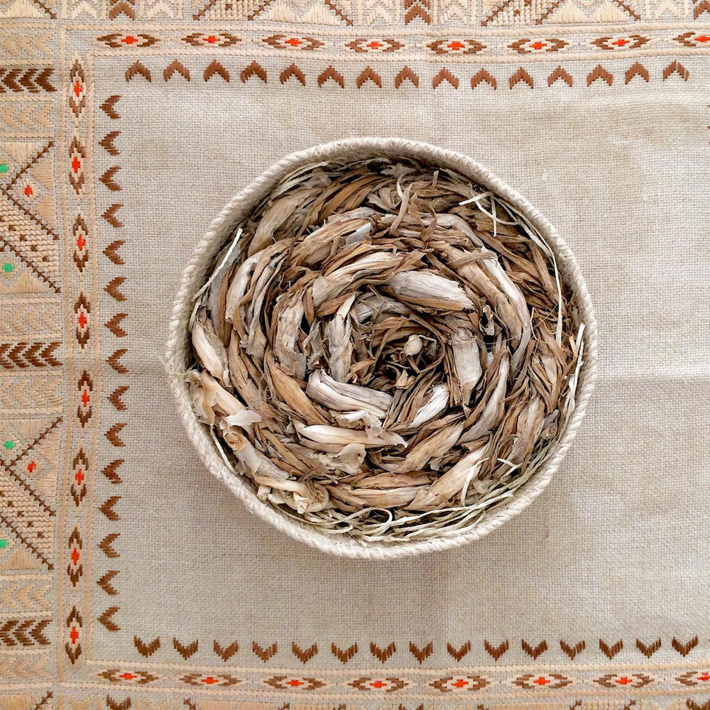 Hand-plaited grasses from rural New Mexico photographed on a traditional Bulgarian embroidery textile. 'Chaguar' basket is made by artisans in Argentina for  NURAXI .