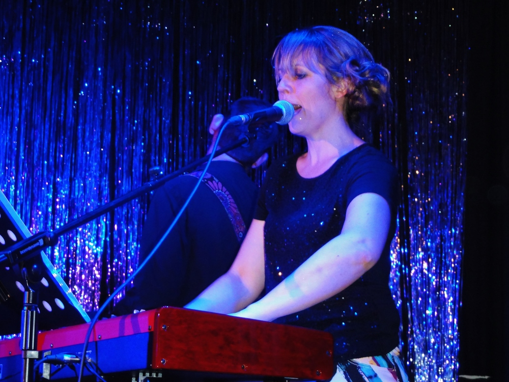 Vic  -   Italian grape admirer Vic has previously performed at the Royal Albert Hall. Her career trajectory now sees her frequently shaking guitar picks out of her keyboard. Vic currently suffers from a recurring nightmare set in Late December, back in '63, involving a half empty bottle of champagne and her hands being replaced by the flippers of a fur seal.