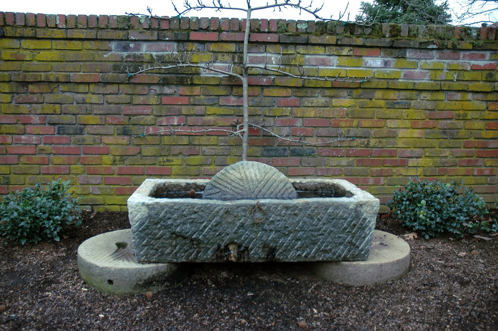 Large millstone base for trough and paver millstone centered in trough
