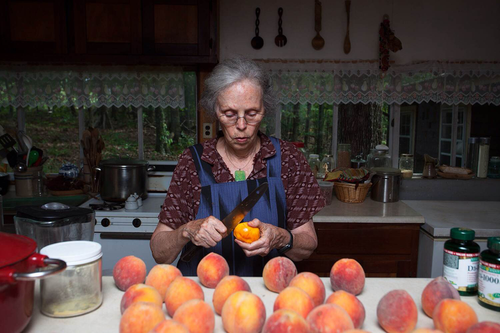 Ina May Gaskin peals peaches in her kitchen.