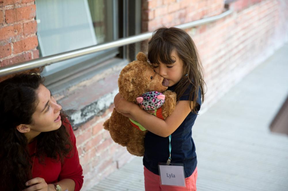 Lyla, right, hugs a stuffed bear as part of the Brave Buddies program.