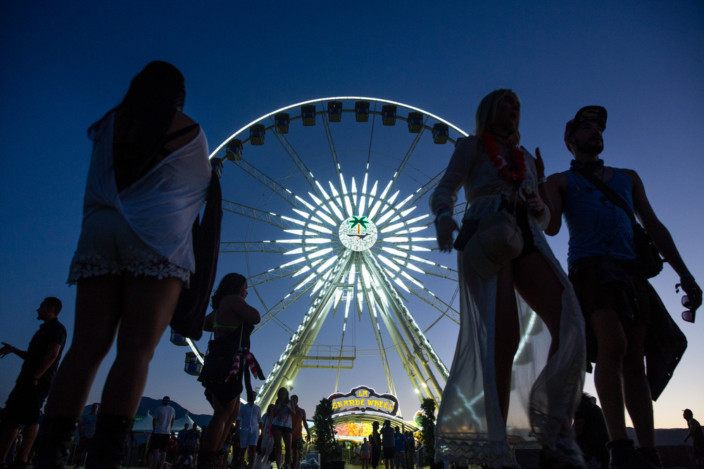 Attendees walk past the Coachella Ferris wheel at the festival entrance.