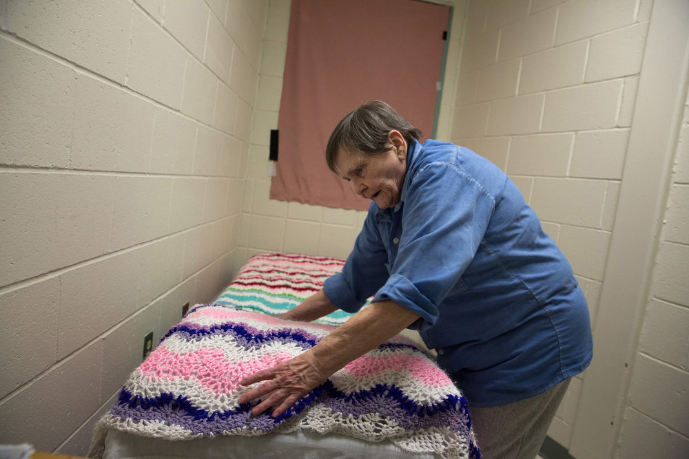 Norma, 76 years old, makes her bed in what used to be a closet. Norma requested to be separated from the younger female prisoners who she says are too loud and give her anxiety. A fellow inmate made this blanket for Norma.