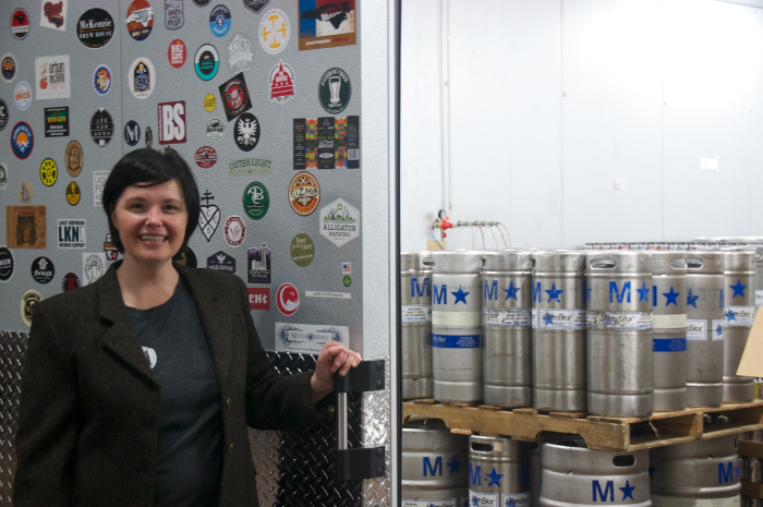 Anita Riley reveals the cold room stash at Mystery Brewing Company while sporting the Riding Jacket