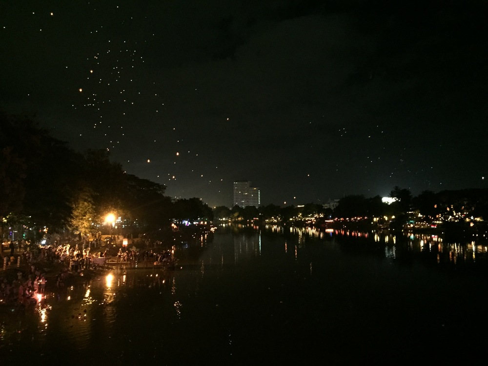 View looking north up the river. People are setting off prayer baskets along the left edge of the river and you can see lanterns from throughout the city above