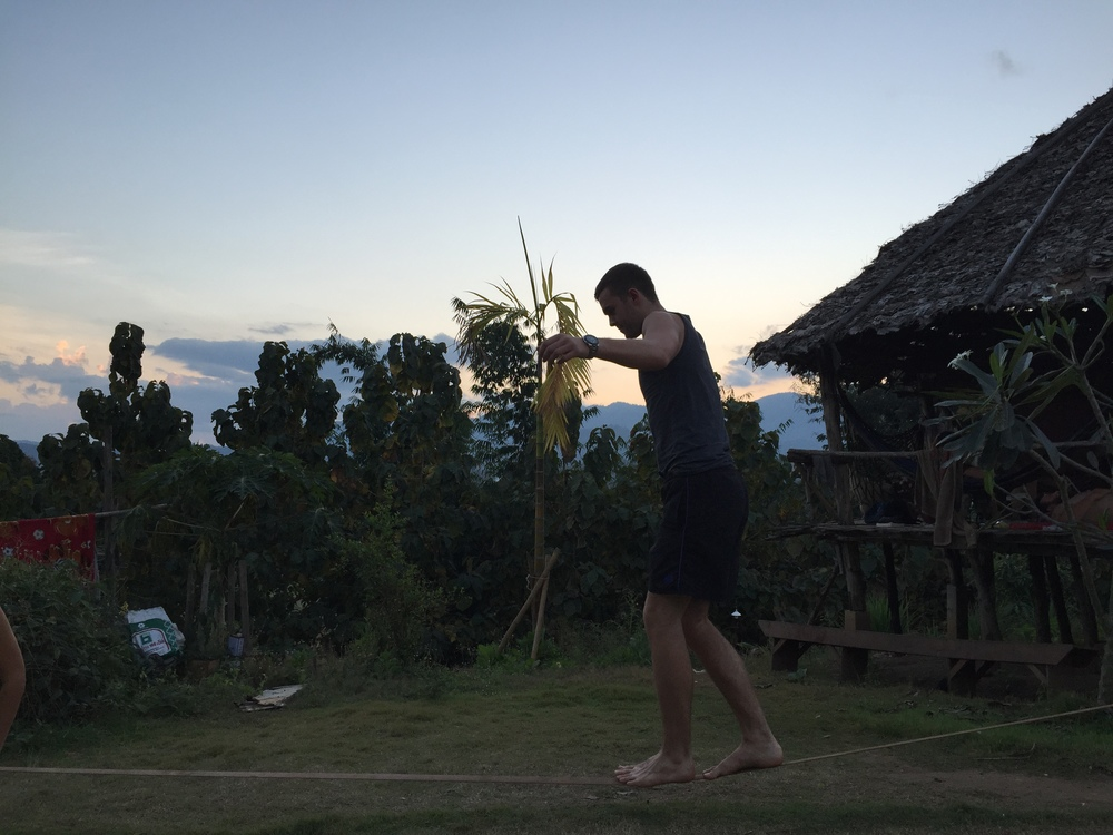 A bit of slack lining practice at sunset on the lawn of the Pai Circus Hostel