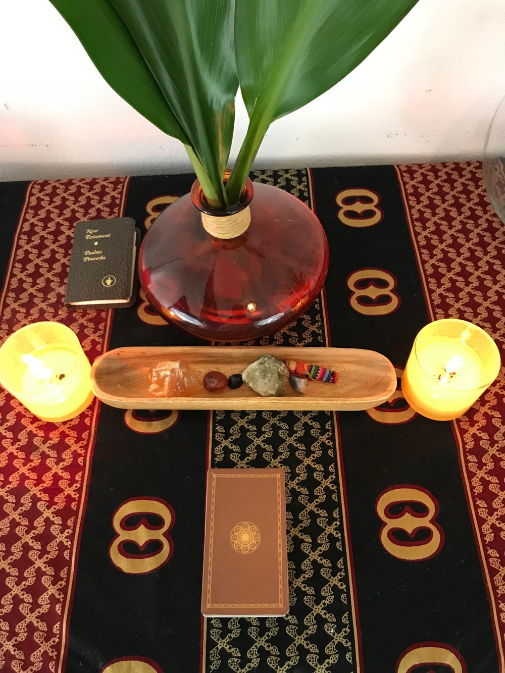 It's All in the Details - So the base of  my alter is an African print fabric. It was gifted to me from a production I worked on. I was gifted different prints but this one spoke to me the most. Since my print is dark I wanted to add lighter pieces to my alter. I found these candles, vase and long wooden bowl from Ross. These candles has an energizing scent and I light them in the morning to start my day.  I love the shape and color of the vase because it adds more character to the space. I chose this wooden piece because it is small and a light color. I only have a few stones and wanted something separate to keep them in. Of course my tarot deck is part of my alter. I have been teaching myself how to read tarot cards. I use to be weary of them because of my Christian upbringing but I've only had positive experiences once I started receiving readings. I'm definitely excited about becoming more familiar with my tarot cards.