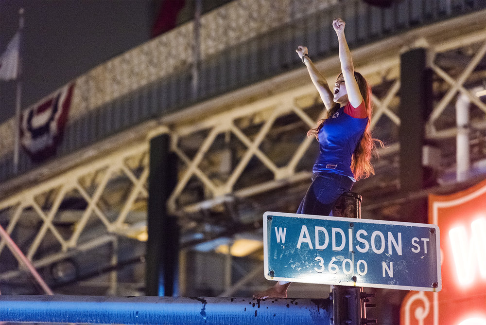 A woman climbed up Addison st. street light to cheer for her team as Game 7 of the World Series continues on Nov. 2nd 2016.
