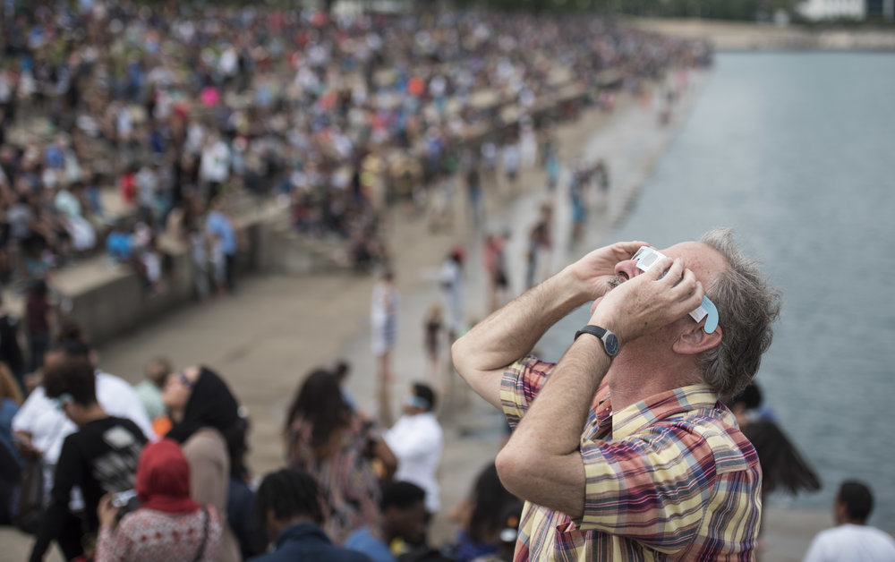 Tim Cash from Minneapolis took a break from his job to watch the solar eclipse outside Adler Planetarium, Monday, Aug. 21, 2017, in Chicago. (AP Photo/G-Jun Yam)