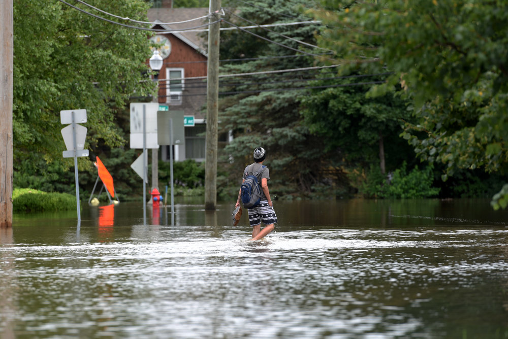 A man passes a flooded street, Friday, July 14, 2017, in Gurnee, Ill. According to Illinois officials flooding in north of Chicago, and the damage is expected to worsen this weekend as water flows down rivers into the state from Wisconsin. (AP Photo/G-Jun Yam)