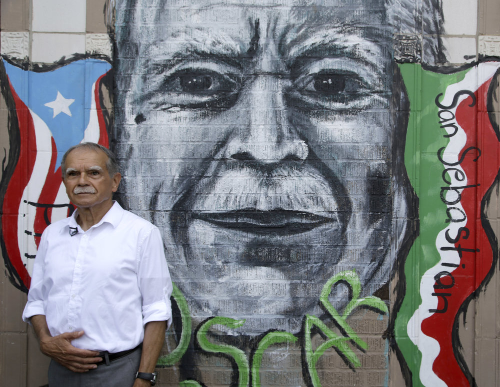 Puerto Rican nationalist Oscar Lopez Rivera poses for a portrait in front of a mural dedicated to him, June 15, 2017, in Chicago. Lopez Rivera, the one-time leader in the Armed Forces of National Liberation, was pardoned by former President Barack Obama in January and freed from house arrest in May after decades in prison. (AP Photo/G-Jun Yam)