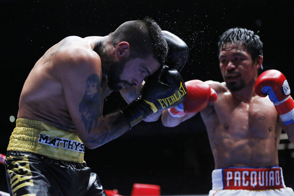 Manny Pacquiao of the Philippines, left, celebrates after defeating Lucas Matthysse of Argentina during their WBA World welterweight title bout in Kuala Lumpur, Malaysia, Sunday, July 15, 2018. (AP Photo/Yam G-Jun)