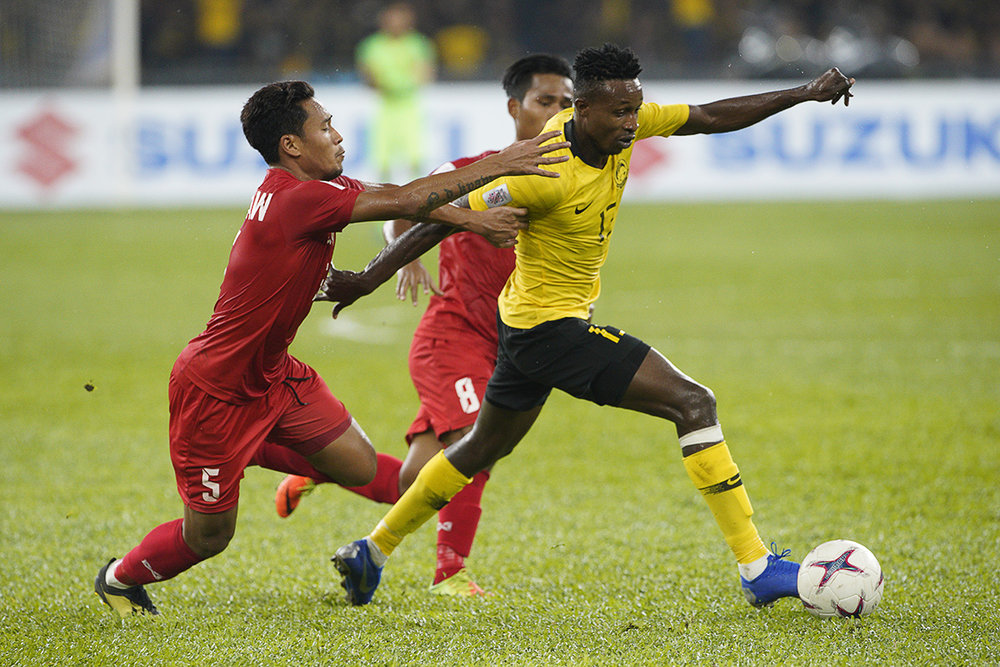 Malaysia's Mohamadou Sumareh, right, battles for the ball with Myanmar Nanda Kyaw and Maung Maung Soe, during the AFF Suzuki Cup at Bukit Jalil National Stadium in Kuala Lumpur, Malaysia, Saturday, Nov. 24, 2018. (AP Photo/Yam G-Jun)