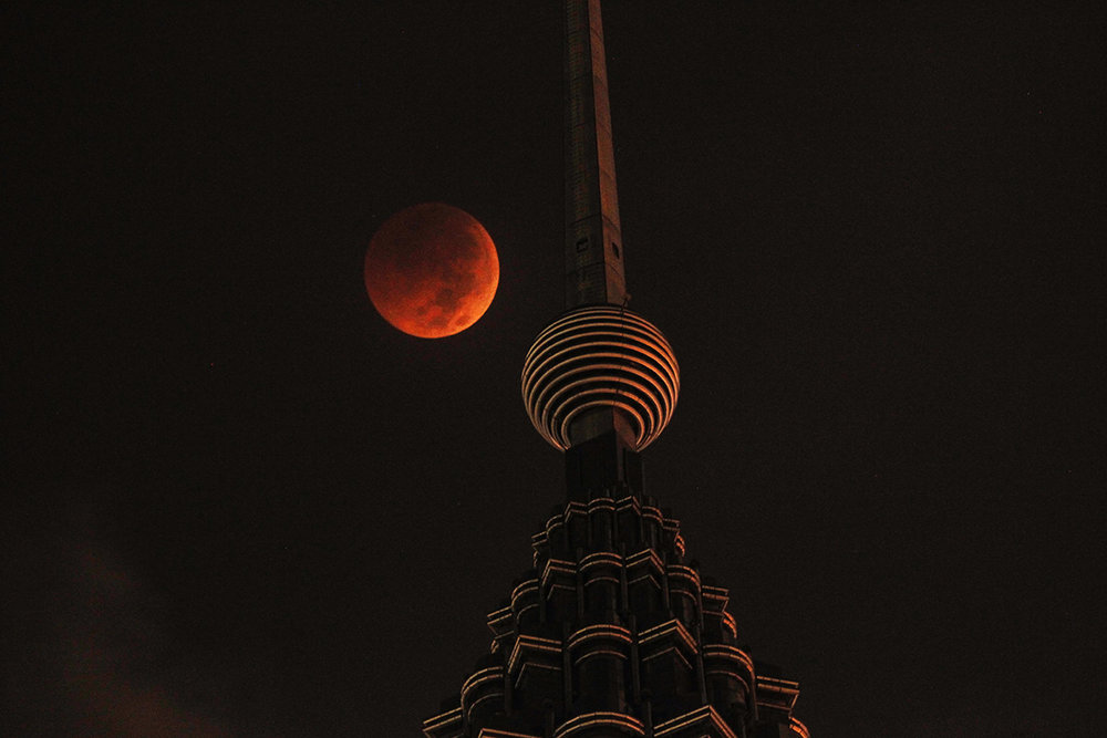 A full moon sets over Petronas Twin Tower during a complete lunar eclipse in Kuala Lumpur, Malaysia, Saturday, July 28, 2018. Skywatchers around much of the world are looking forward to a complete lunar eclipse that will be the longest this century. (AP Photo/Yam G-Jun)