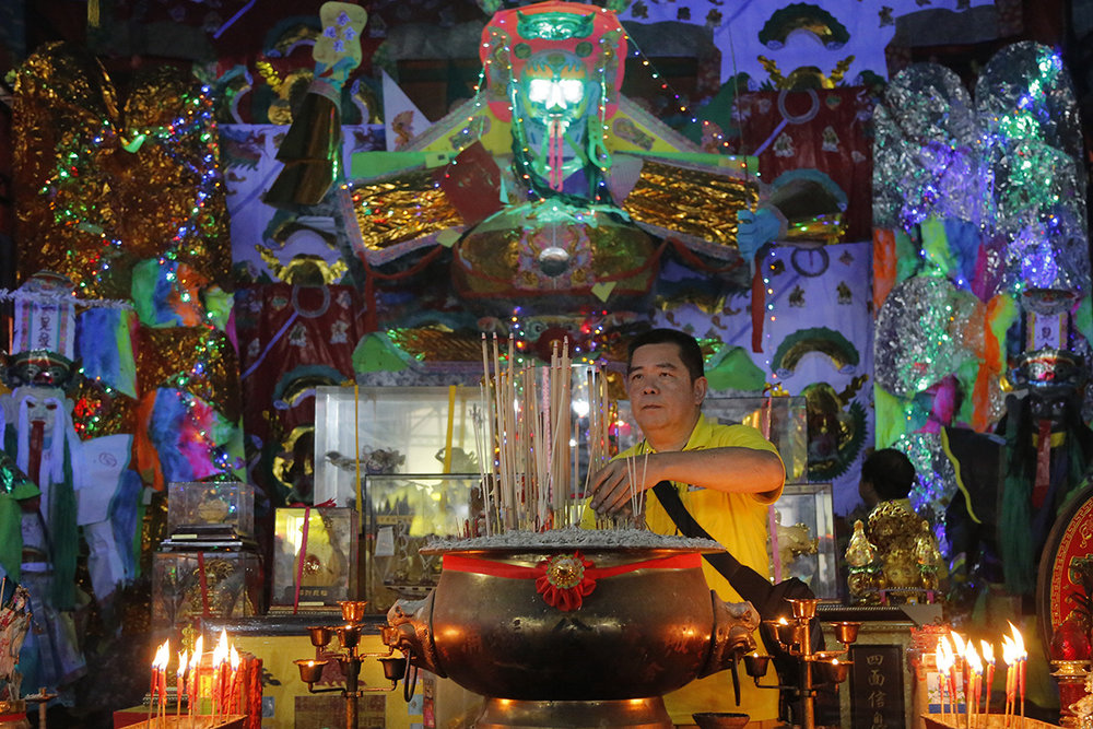 """In this Aug. 16, 2018, photo, a man collects joss sticks in front of a giant paper statue of the Chinese deity """"Da Shi Ye"""" or """"Guardian God of Ghosts"""" during the Chinese Hungry Ghost Festival in Puchong, Malaysia. (AP Photo/Yam G-Jun)"""