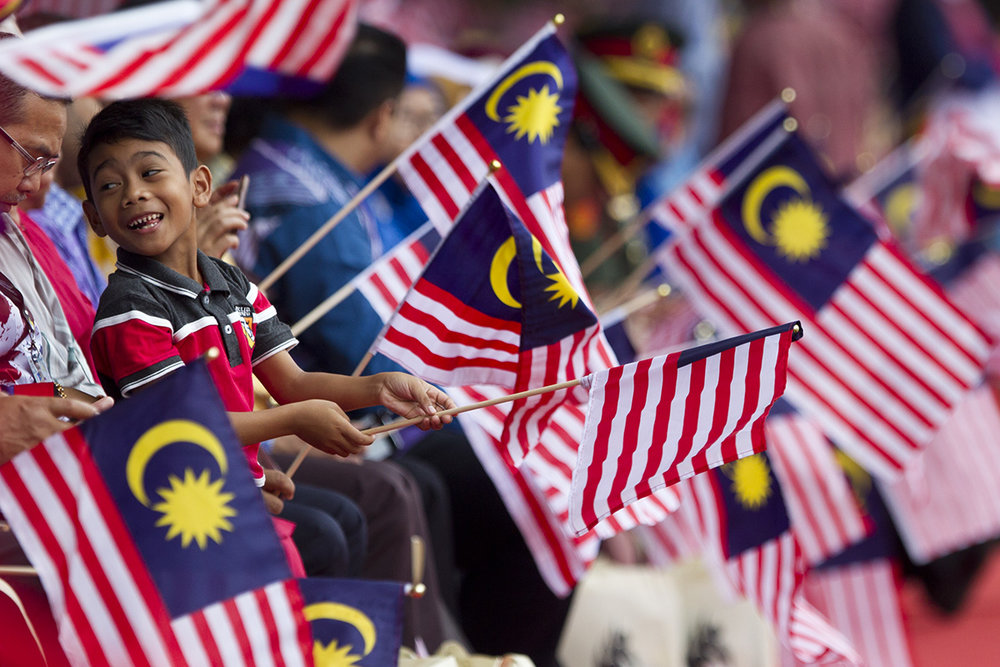 Malaysian waves national flags during the 61st National Day celebrations in Putrajaya, Malaysia, Friday, Aug. 31, 2018. The Federation of Malaya gained its independence from Britain on Aug. 31 in 1957. (AP Photo/Yam G-Jun)
