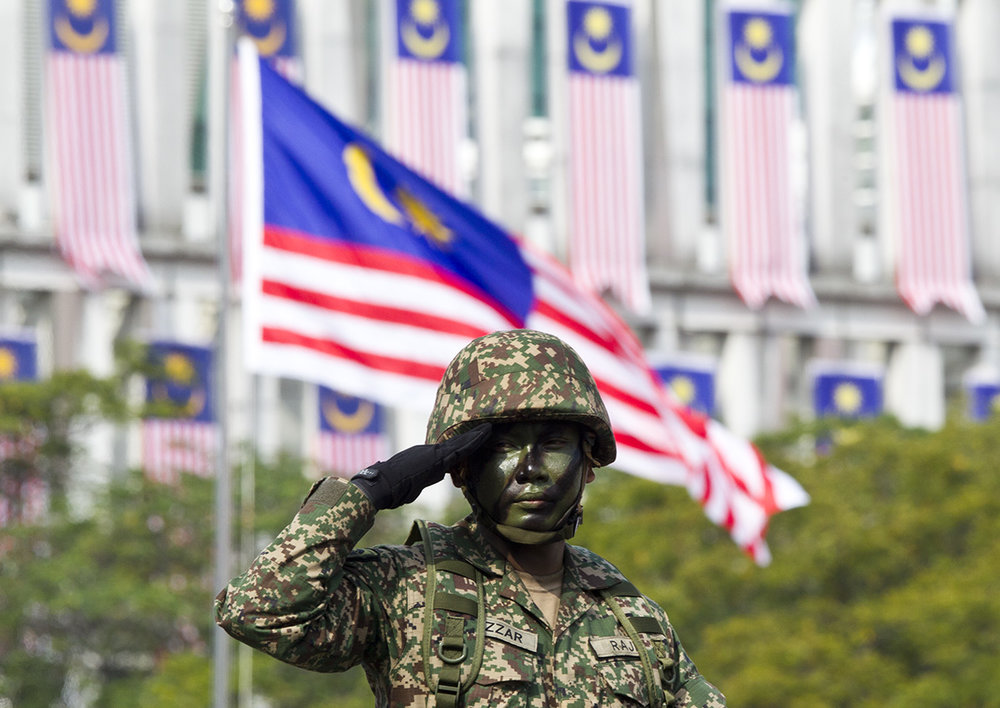 Malaysian military personnel salutes during the 61st National Day celebrations in Putrajaya, Malaysia, Friday, Aug. 31, 2018. The Federation of Malaya gained its independence from Britain on Aug. 31 in 1957. (AP Photo/Yam G-Jun)