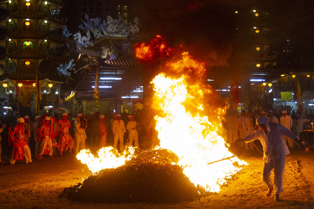 In this Wednesday, Oct. 17, 2018, file photo, A Malaysian ethnic Chinese men prepares the burning coals on the final day of the Nine Emperor Gods Festival at a temple in Ampang, Malaysia. (AP Photo/Yam G-Jun, File)