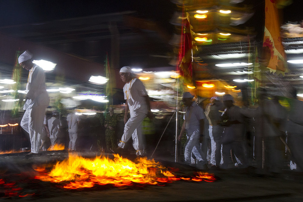In this Wednesday, Oct. 17, 2018, file photo, Malaysian ethnic Chinese men walk barefoot on a bed of burning coals on the final day of the Nine Emperor Gods Festival at a temple in Ampang, Malaysia. (AP Photo/Yam G-Jun, File)