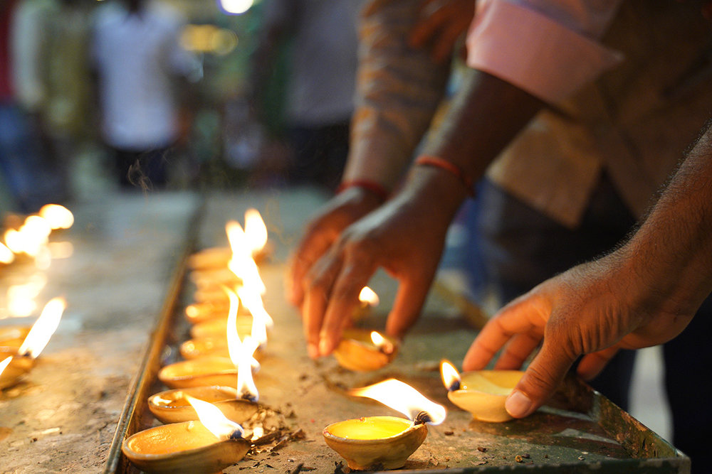 Hindu devotees light clay oil lamps while praying at a temple during the Deepavali celebration in the Batu Caves, Selangor, Malaysia, Tuesday, Nov. 6, 2018. (AP Photo/Yam G-Jun)