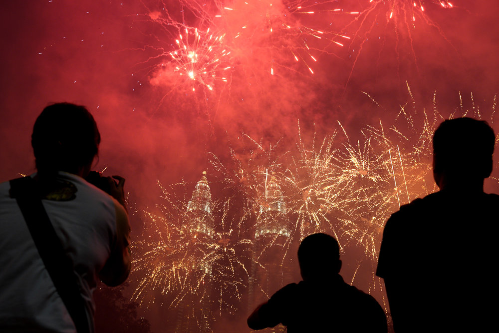 In this Tuesday, Jan. 1, 2019, file photo, spectators watch as fireworks explode in front of Malaysia's landmark building, the Petronas Twin Towers, during the New Year's celebration in Kuala Lumpur, Malaysia. (AP Photo/Yam G-Jun, File)