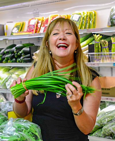 Jacqueline Church of Boston Chinatown Tours holding Chinese chives at an Asian super market.